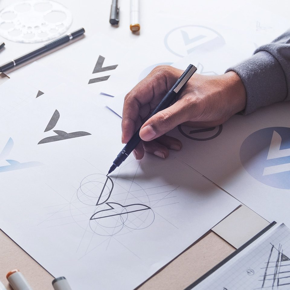 Person drawing shapes on a paper with a black pen