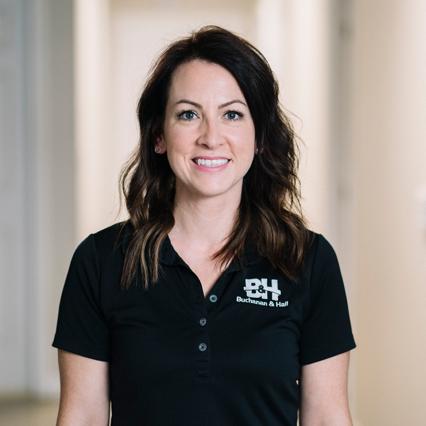 Headshot of a smiling female employee in a dark blue polo shirt, with a BH logo on the one side of her shirt