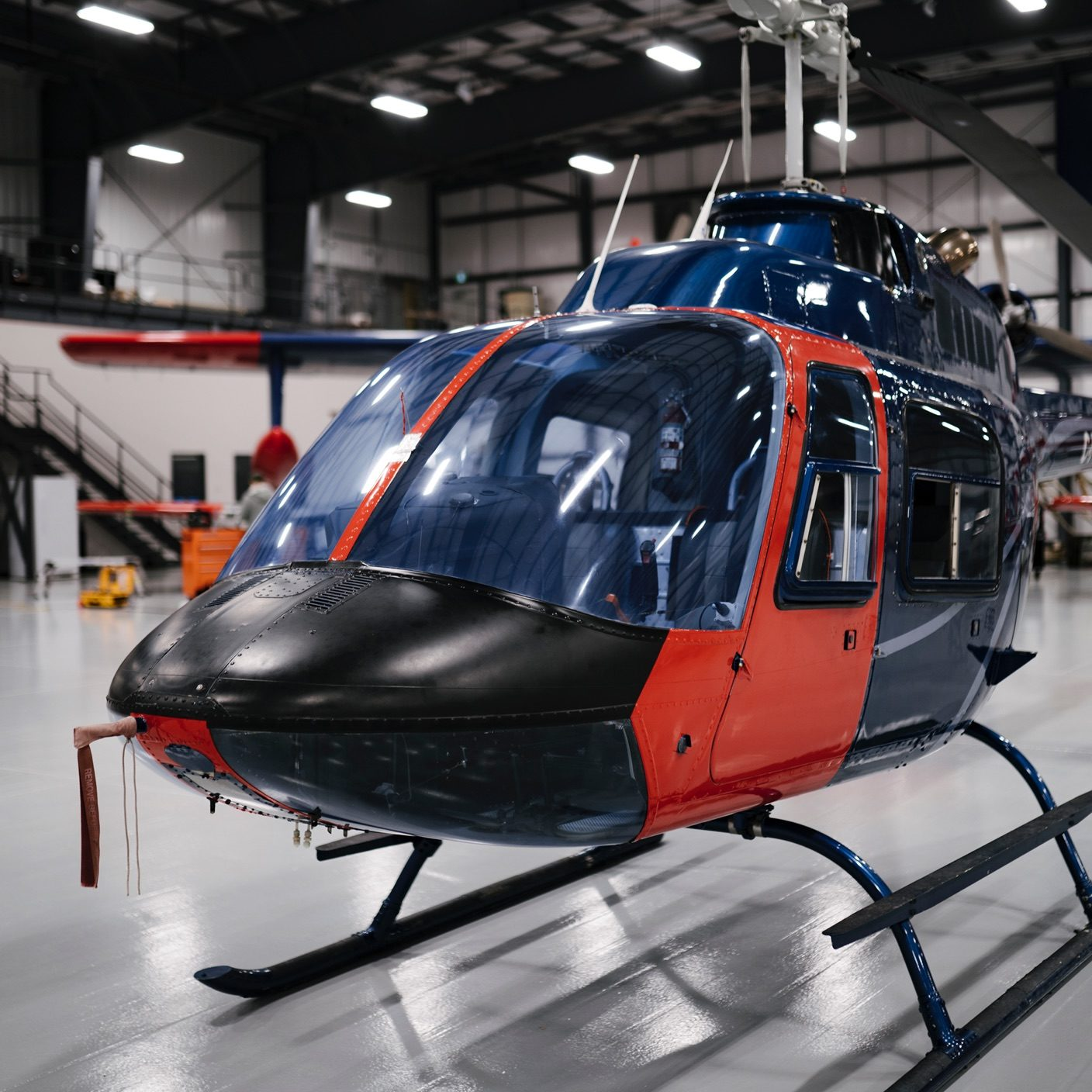 blue and red helicopter in a warehouse