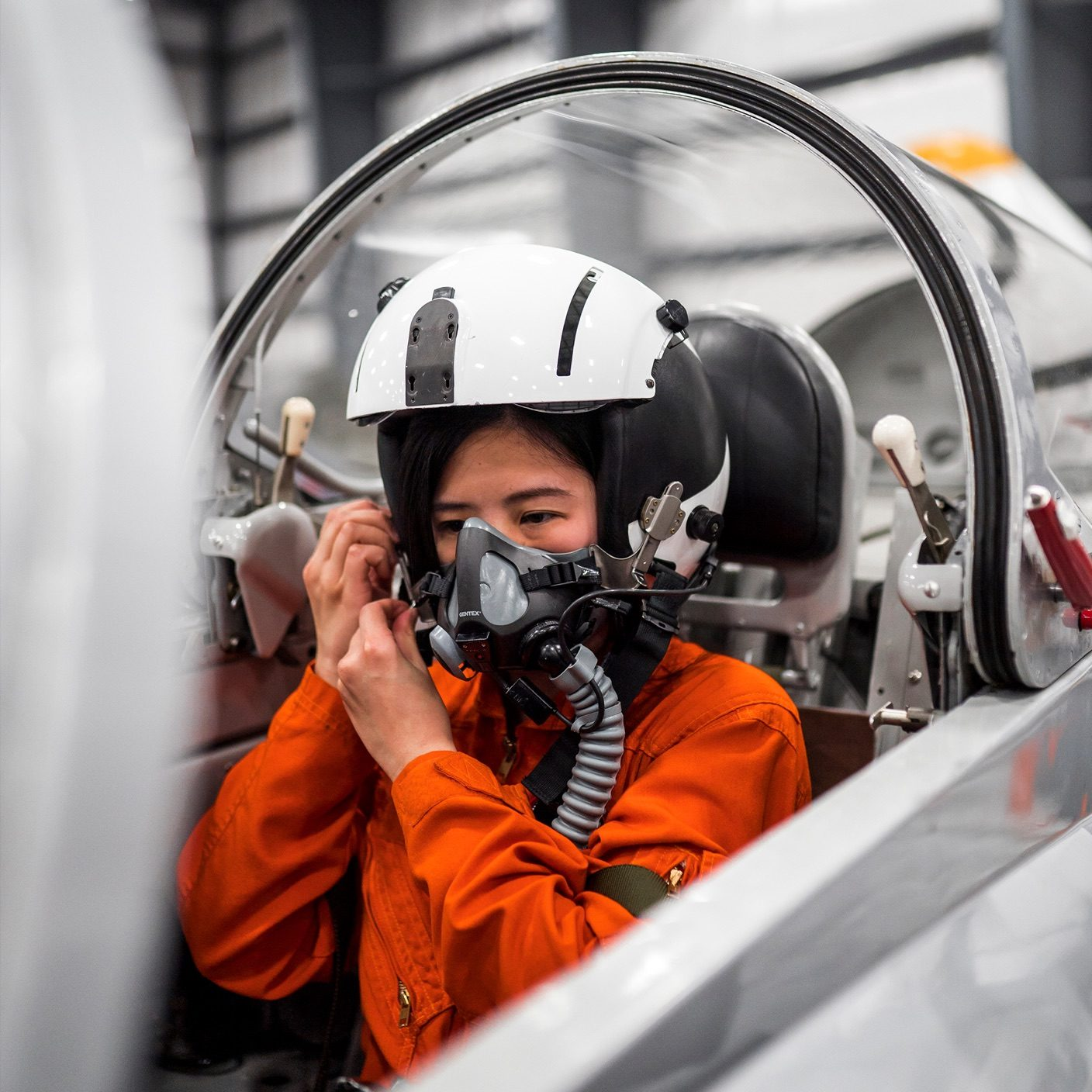 pilot in an orange suit putting on her helmet getting ready for takeoff